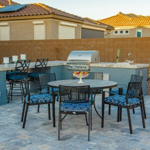An outdoor living space with a grill island and seating area