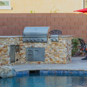 An outdoor kitchen with a BBQ grill next to a pool