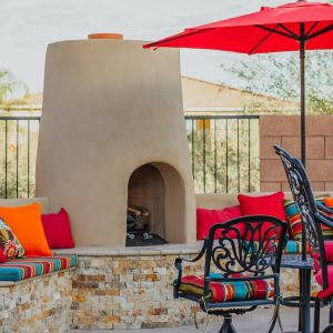 A Tucson poolside fire pit with vibrant cushions and a built-in seating area