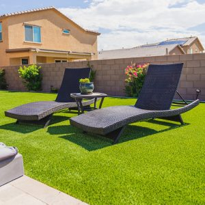 A poolside seating area with artificial grass