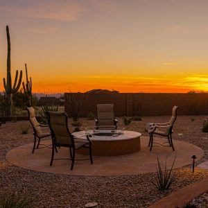A fire pit and outdoor living area with a Tucson sunset in the background