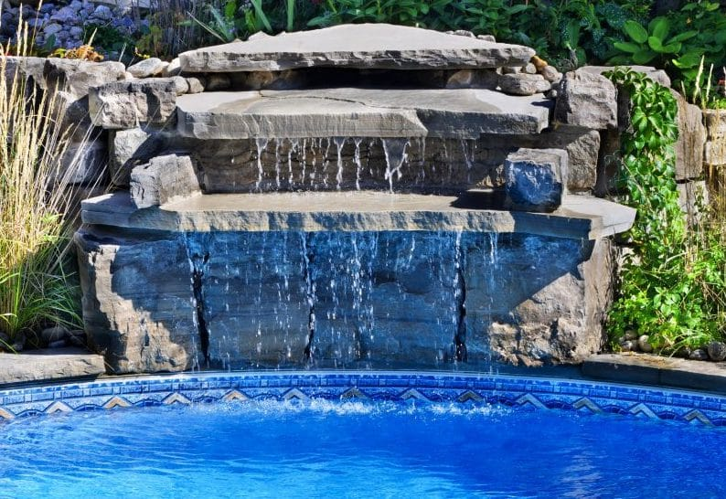 A waterfall in an inground pool
