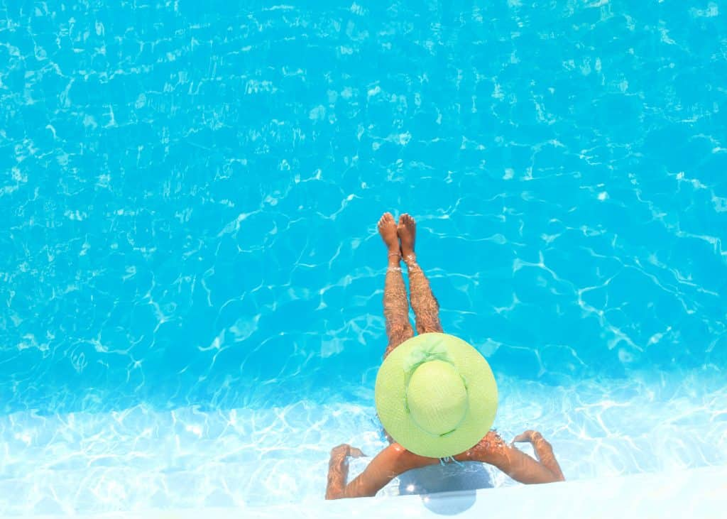 A woman in a green sun hat lounging in a swimming pool
