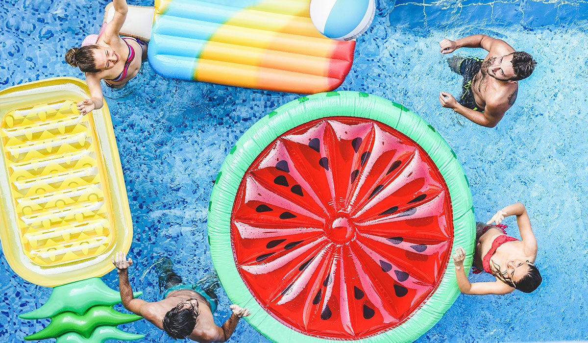 A group of people in a swimming pool with inflatable pool floats