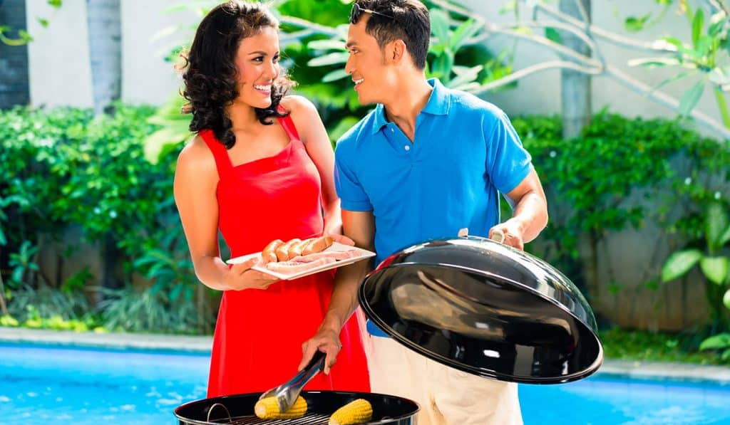 A woman and a man laughing by an outdoor BBQ