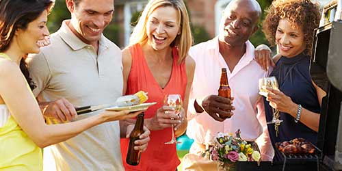 A group of friends laughing while grilling in an outdoor kitchen