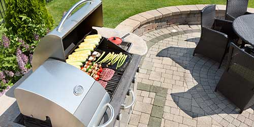 Kebabs and vegetables grilling on an outdoor grill