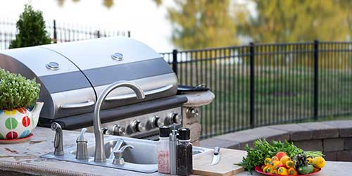 An outdoor kitchen with a BBQ grill