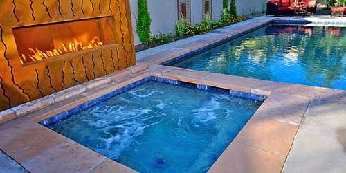 A custom swimming pool with a fire fit and a hot tub