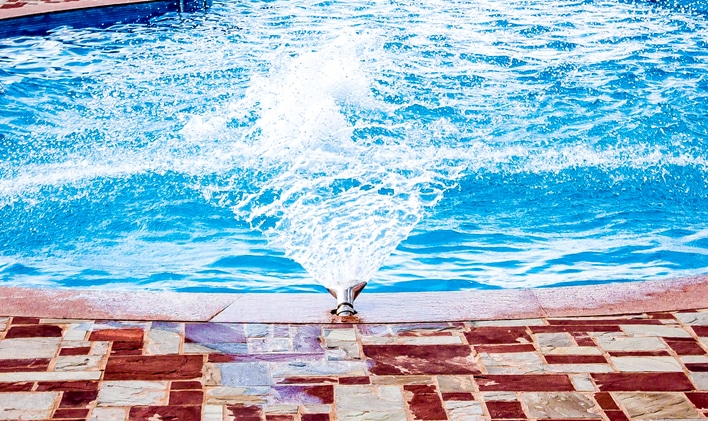 Water spraying into a pool, one of your many options for pool fountains