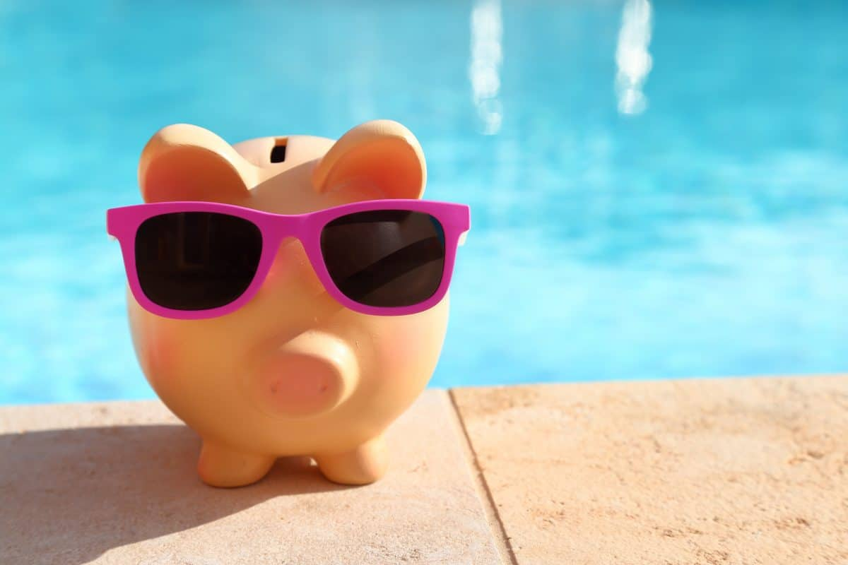 A piggy bank next to a pool, representing the cost of salt water pools
