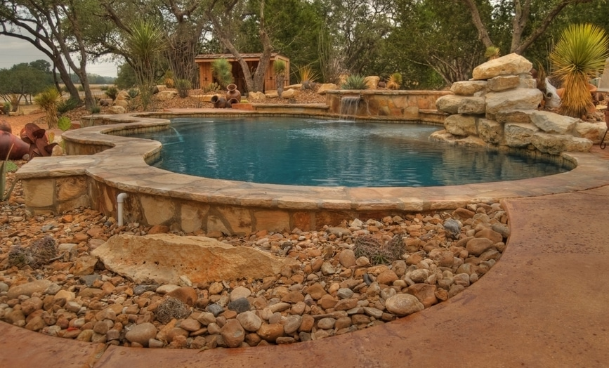A simple landscape design around a pool, featuring rocks and desert plants
