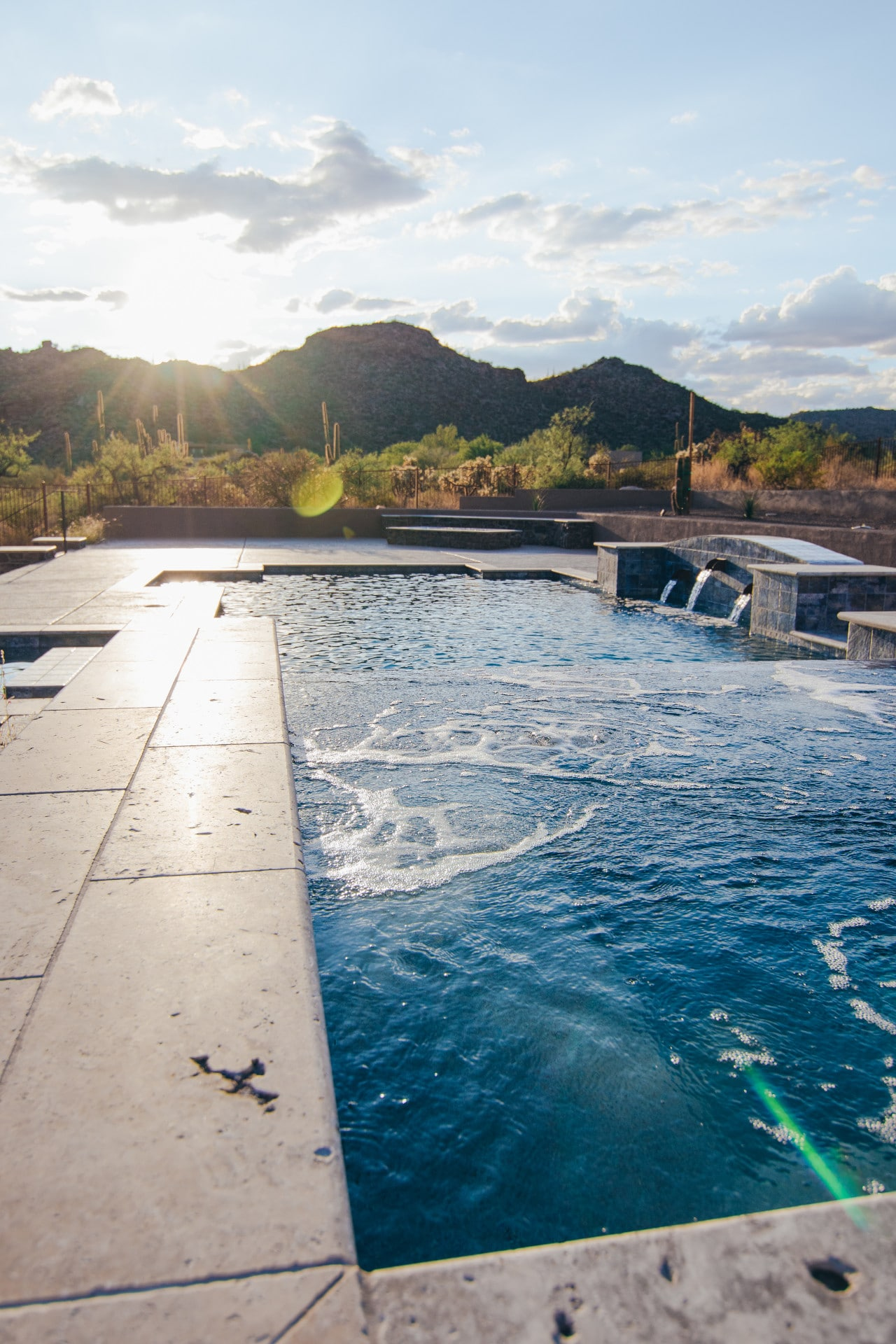 Closeup of a spillover spa next to the pool with sun shining in the background over the mountains