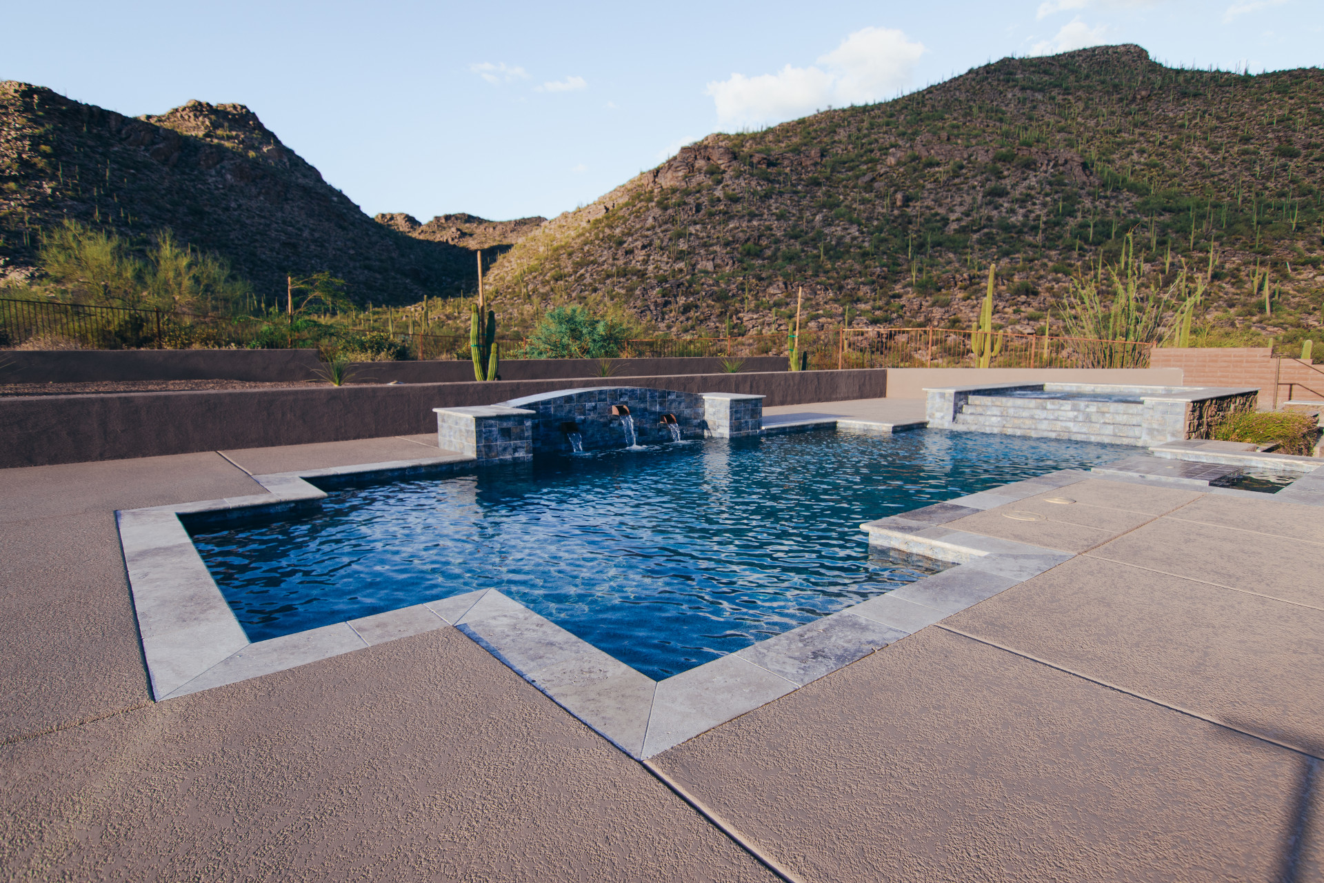 Custom pool with water fall features and spillover spa with steps leading into the pool