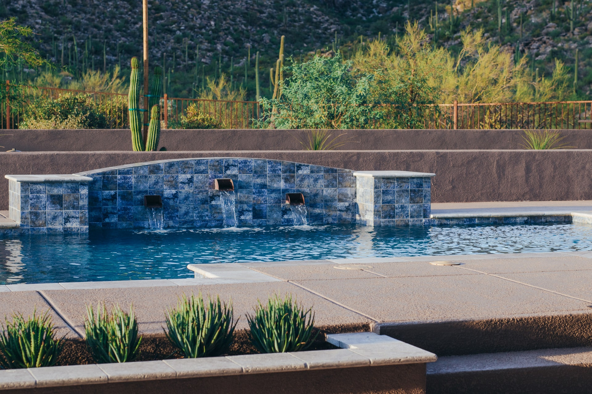 Side view of a custom waterfall with three water outlets pouring into a pool