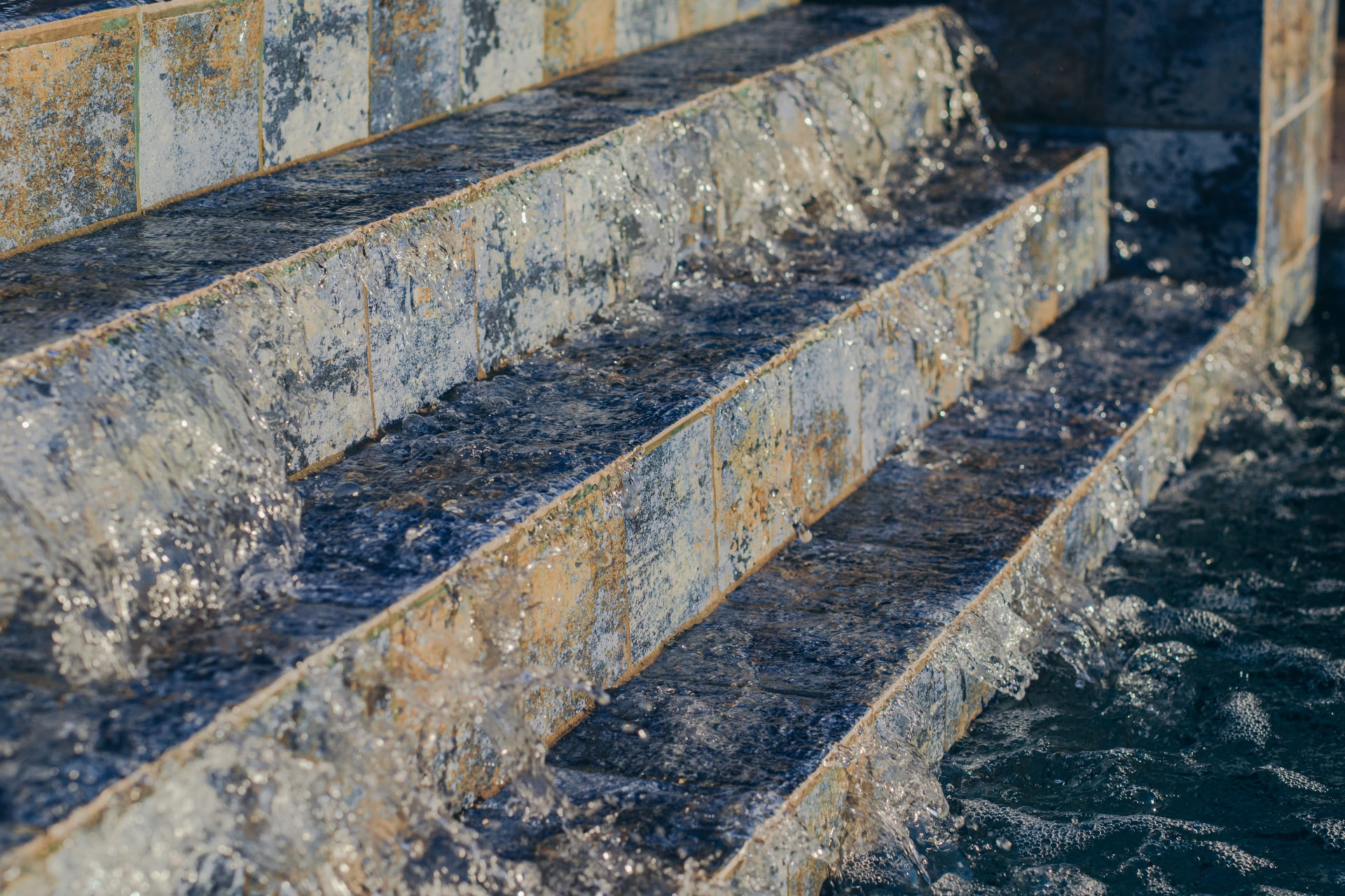 Closeup of steps leading down into a pool with water running down the steps.