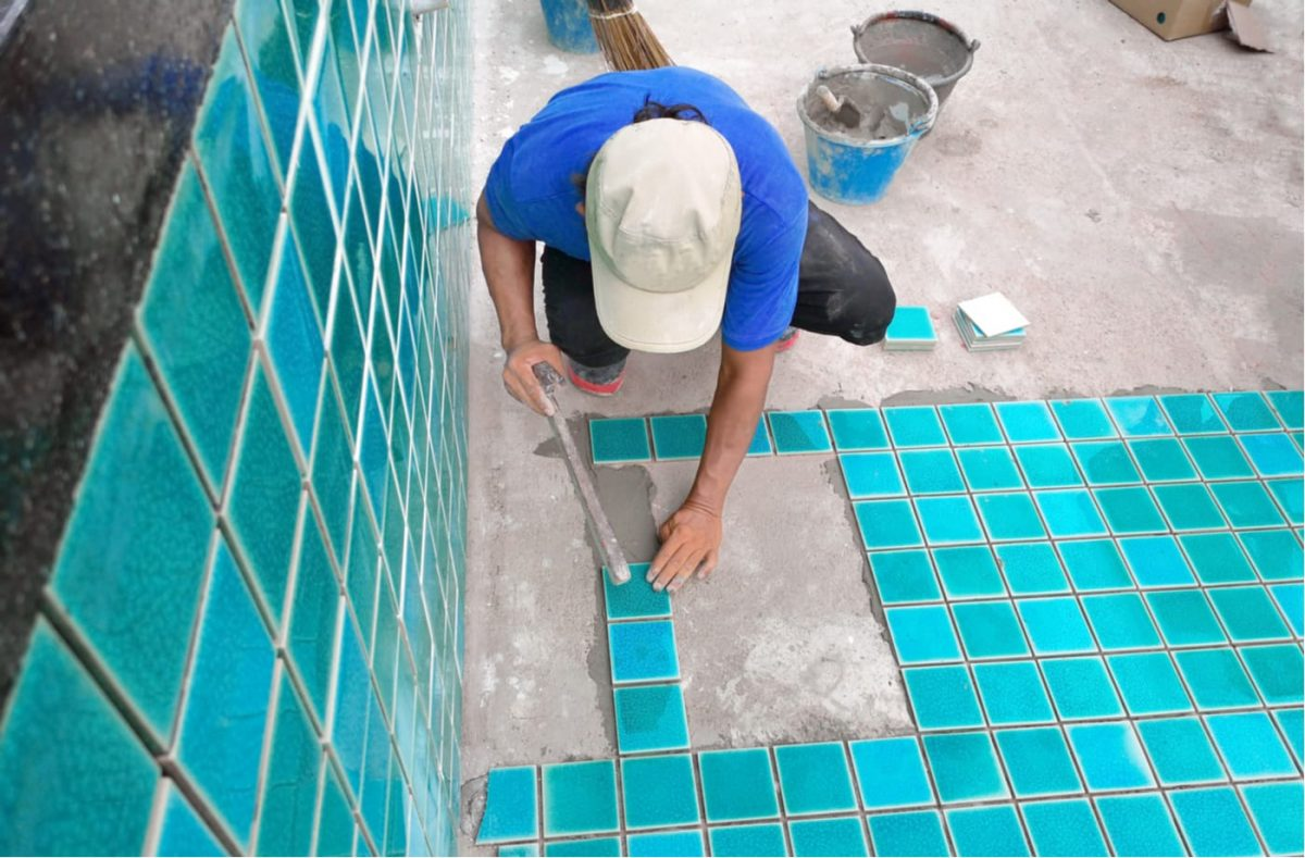 A Tucson pool builder laying blue pool tiles