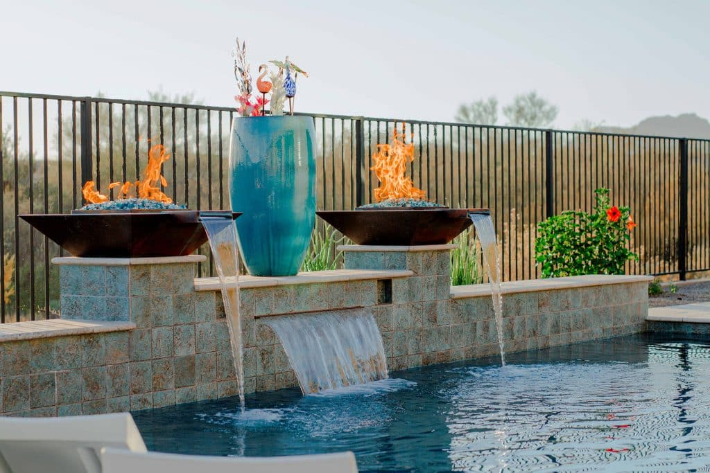 A lovely pool design we created with fire pits, fountains, and a rain curtain