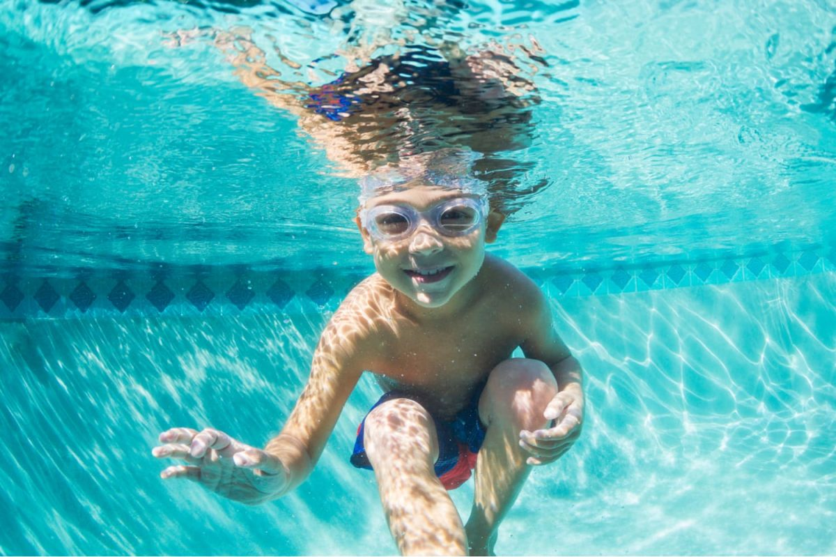 A kid in a pool underwater; children are one factor in choosing large vs small pools