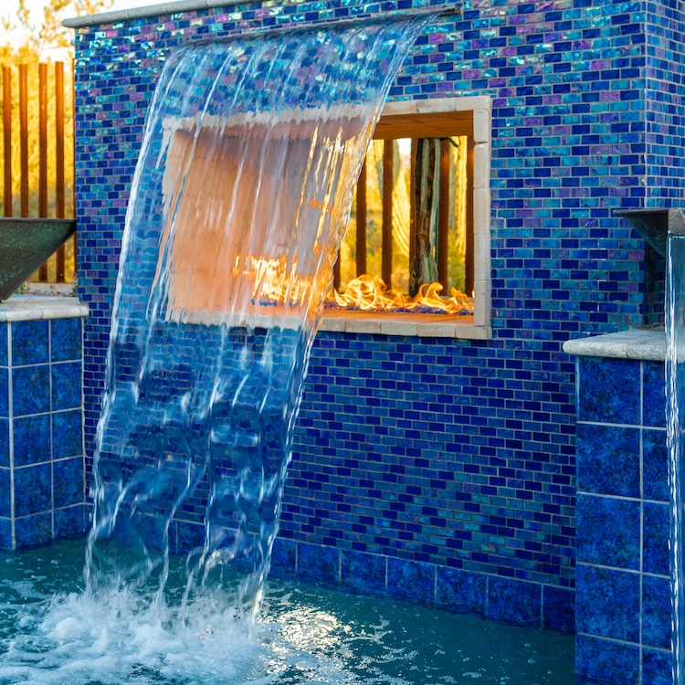 A rain curtain, a popular pool water feature, falling over a fire pit with colorful pool tiles