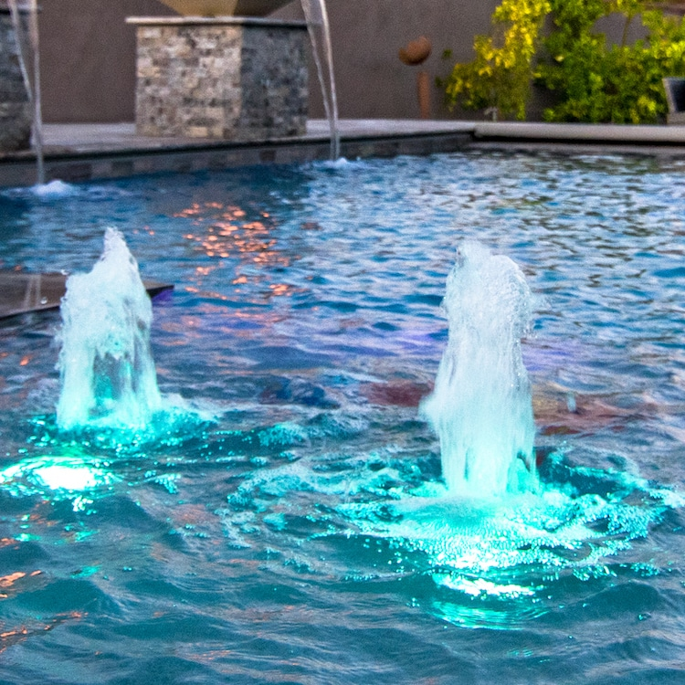 Pool water features known as gushers with blue LED lights under them