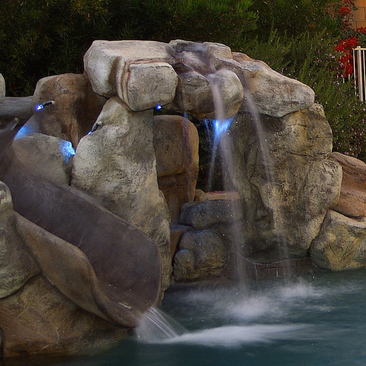 A grotto with a natural rock waterslide in a luxury pool