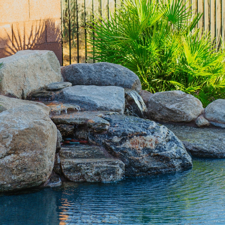 A waterfall made with natural rocks, a popular pool water feature