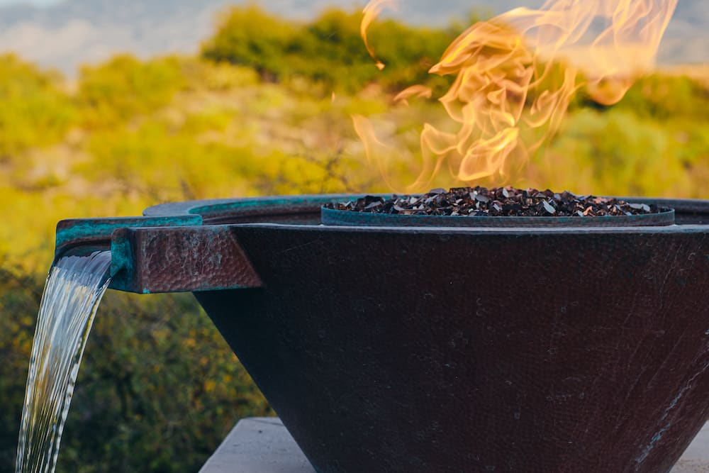 A metal pool fire bowl with a fountain flowing from it