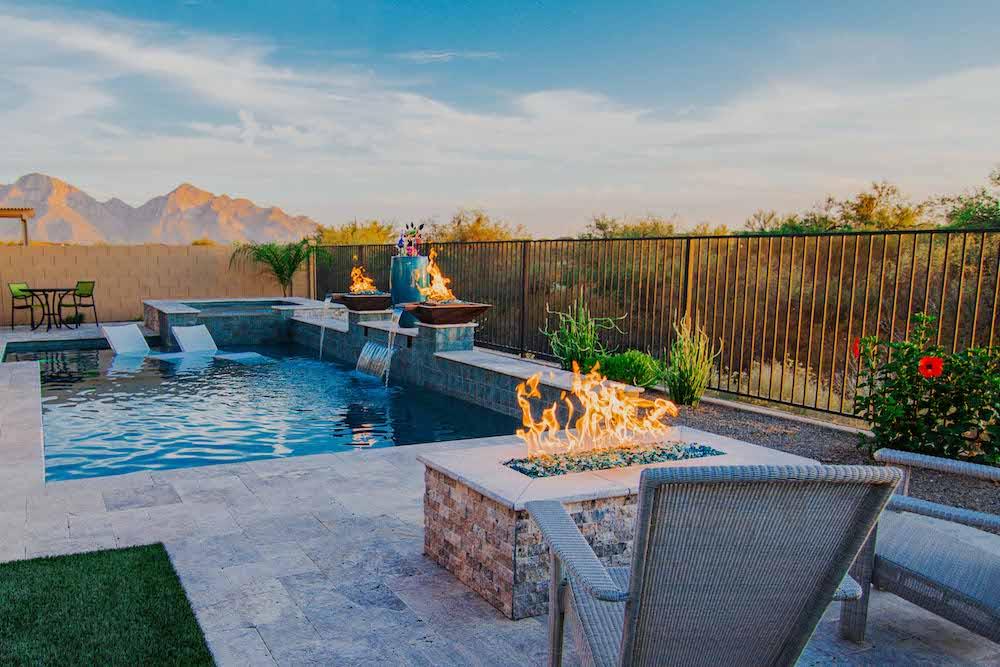 A custom pool in Tucson, AZ with a fire pit and pool fire features integrated with fountains