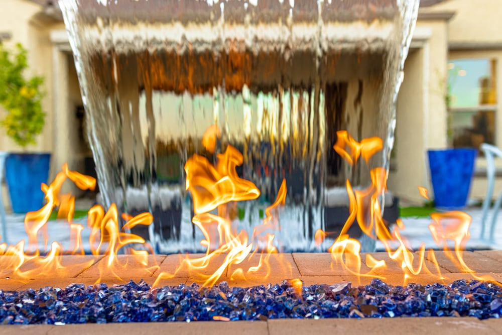 A pool fire feature with blue glass fragments and water flowing over the back