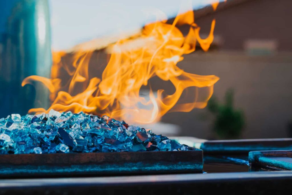 A close up a pool fire feature with blue glass fragments built by our Tucson pool builders