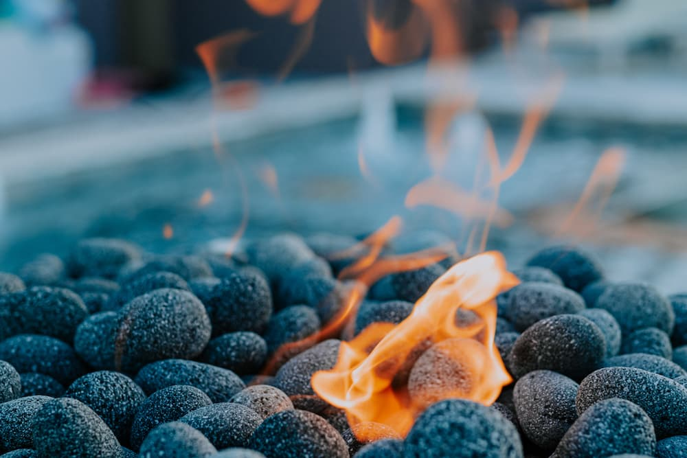 A close-up of lava stones in one of the pool fire features our team has built