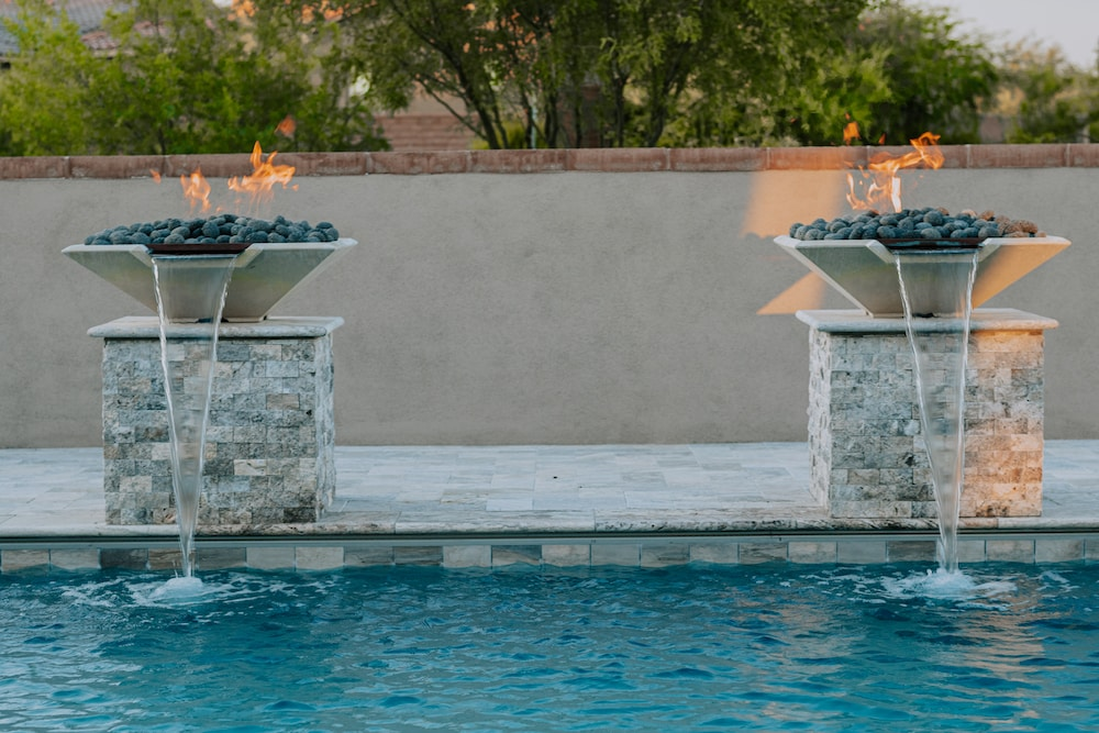 Twin fire pillars pouring water into a custom luxury pool in Tucson