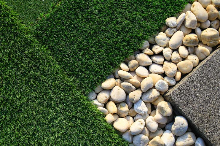 Artificial grass next to a rock design, one of many landscaping ideas for a clean and green backyard