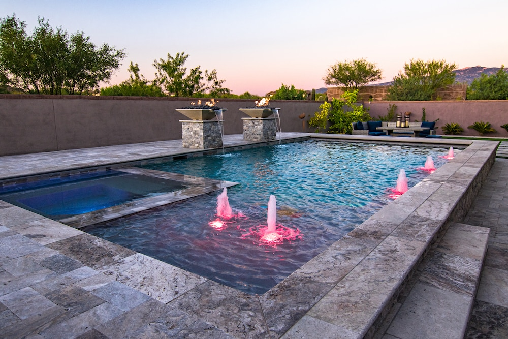 A modern rectangular pool with colorful LED lights and pool fountains