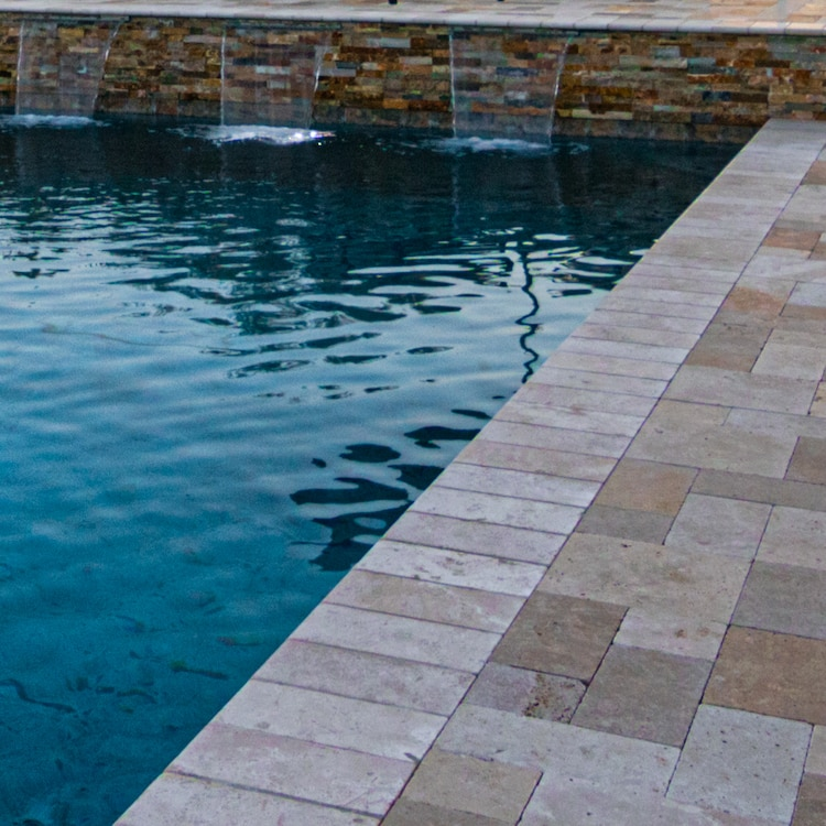 The stone tile deck of one our modern pools