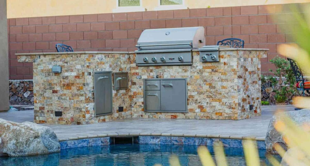 An outdoor grill island next to a pool