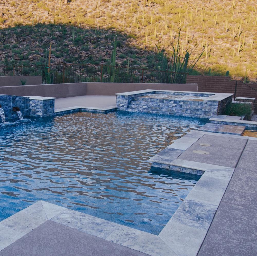 A contemporary pool design with a spillover spa