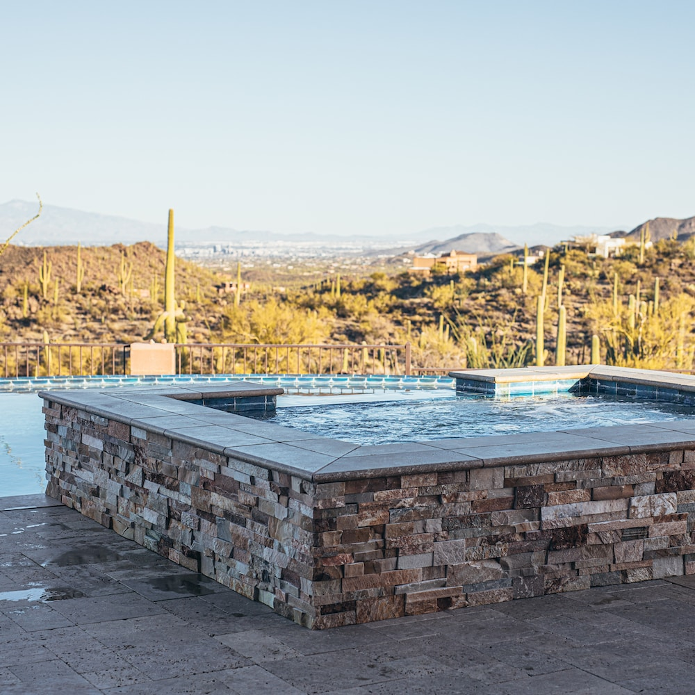 The back of an in-ground spa with stonework