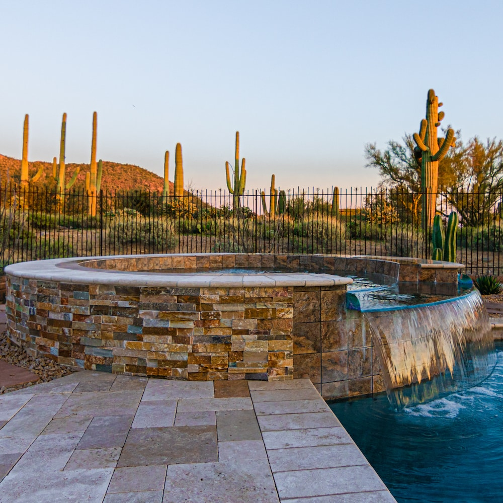 A spillover spa idea with stone tiles and a travertine deck